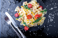 Pasta salad in slate plate with tomatoes cherry, tuna, corn and arugula near knife and spoon. Top view. ingredients. Italian food. Stock Images