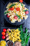 Pasta salad in slate plate with tomatoes cherry, tuna, corn and arugula. Top view. ingredients. Italian food. Royalty Free Stock Photo