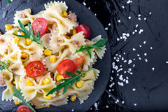 Pasta salad in slate plate with tomatoes cherry, tuna, corn and arugula. Top view. Italian food. Pasta salad in slate plate with tomatoes cherry, tuna, corn and Stock Photos
