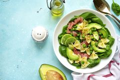Pasta salad with spinach,avocado,salted salmon and green pea.Top. Pasta salad with spinach,avocado,salted salmon and green pea in a white bowl over light blue Stock Image