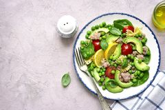 Pasta salad with spinach,avocado,salted salmon and green pea.Top. Pasta salad with spinach,avocado,salted salmon and green pea in a white bowl over light blue Royalty Free Stock Photo