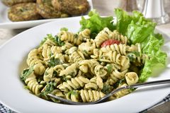 Pasta salad and spinach cakes. Closeup of a Spinich pasta salad with rotini pasta and spinach cakes in the background stock photo