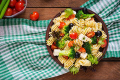Pasta salad. With tomato, broccoli, black olives, and cheese feta. Top view royalty free stock images