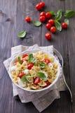 Pasta salad with tomato, mozzarella, pine nuts and basil Stock Photos