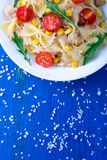 Pasta salad with tomatoes cherry, tuna, corn and arugula on blue wooden background. Top view. Pasta salad with tomatoes cherry, tuna, corn and arugula on blue Stock Photos