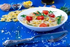 Pasta salad with tomatoes cherry, tuna, corn and arugula. Close up. Royalty Free Stock Photos