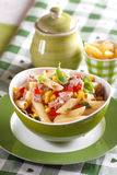 Pasta salad with tuna and corn. In green bowl stock image