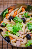 Pasta salad with tuna and olives. Bowl of pasta salad with tuna, olives, lettuce and carrots stock photo