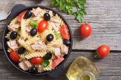 Pasta salad with tuna. Tomatoes and olives in pan stock image