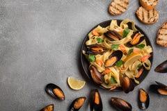 Pasta saporita con le cozze, il calamaro, il prezzemolo ed il limone, vista superiore fotografie stock libere da diritti