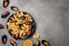 Pasta saporita con le cozze, il calamaro, il prezzemolo ed il limone, vista superiore fotografia stock