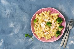 Pasta with sauce and broccoli on a blue background. Top view, copy space