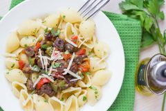 Pasta with sauce chicken hearts, vegetables, red paprica, green Stock Image
