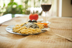 Pasta with sauce pesto,  parmesan cheese, black olives and a gla Royalty Free Stock Image