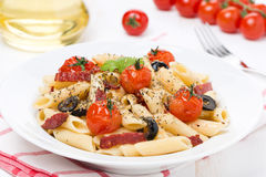 Pasta with sausage, cherry tomatoes and olives on the plate Royalty Free Stock Photography