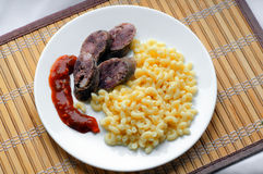 Pasta with sausage and ketchup Stock Image