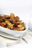 Pasta, sausage and sauce. Tablet setting with a bowl full of rigatoni or penne pasta and sliced sausage in a tomato sauce Royalty Free Stock Photos