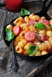 Pasta with sausages in tomato sauce with basil and cheese Stock Image