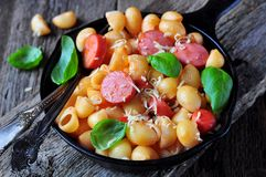 Pasta with sausages in tomato sauce with basil and cheese Royalty Free Stock Image