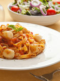 Pasta with scallop and tomato sauce Stock Images