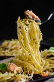 Pasta with seafood in a creamy sauce wrapped on a fork rises fro. M the plate. Italian cuisine, pasta with mussels and shrimps royalty free stock image
