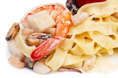 Pasta with seafood. Isolated on white. Healthy dinner with shrimps, mussels and tiny octopuses Royalty Free Stock Photo