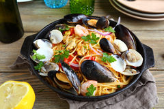 Pasta with seafood and lemon in a frying pan Stock Photo