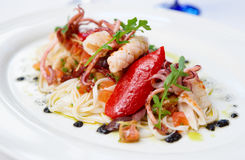 Pasta with seafood on oval porcelain plate Stock Images