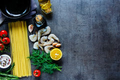 Pasta with seafood. Vintage kitchen table and ingredients for pasta with seafood. Shrimps, spaghetti, dill, garlic, spices and cherry-tomatoes over grunge Stock Photos
