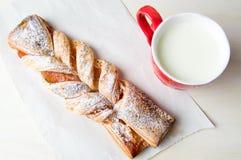 Pasta sfoglia intrecciata con inceppamento e bicchiere di latte fotografia stock libera da diritti