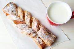 Pasta sfoglia intrecciata con inceppamento e bicchiere di latte immagini stock libere da diritti