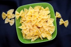 Pasta in the shape of a bow in a green bowl on a blue background stock photo