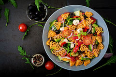 Pasta in the shape heart salad with tomatoes, cucumbers, olives, mozzarella and red onion Stock Photo
