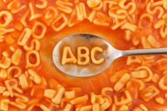 Pasta shaped ABC letters in tomato sauce on a spoon Stock Photos
