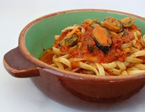 Pasta with shelled mussels in a tomato sauce Stock Photo
