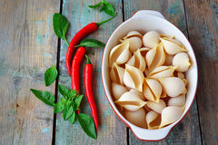 Pasta shells in ceramic form, chili pepper and basil on a wooden. Background Royalty Free Stock Image