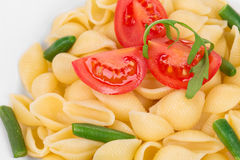 Pasta shells with vegetables on white plate Stock Photos