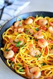 Pasta and shrimp in a pan. Pasta and shrimp dinner in a pan on light background stock photography