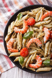 Pasta with shrimp, tomato and pesto sauce close-up. vertical top Royalty Free Stock Photography