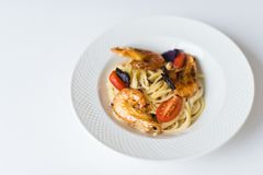 Pasta with shrimp in a white plate. Top view, white background. royalty free stock images
