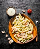 Pasta with shrimp in a wooden plate and the sauce in a bowl royalty free stock images