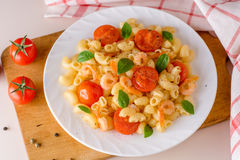 Pasta with shrimps, cherry tomatoes and basil in white plate. Stock Photography