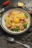 Pasta spaghetti alla carbonara close-up with ham, cheese and raw egg on a dark background. Top view stock photo