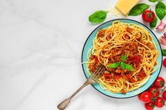 Pasta spaghetti bolognese on a blue plate with fork on white marble table. healthy food. top view