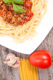 Pasta. Spaghetti bolognese,some tomato, garlic, and raw pasta on a wooden background stock photo