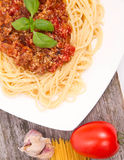 Pasta. Spaghetti bolognese,some tomato, garlic, and raw pasta on a wooden background Royalty Free Stock Image