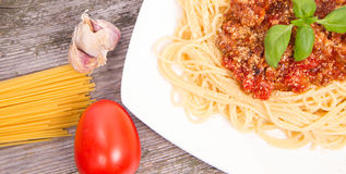 Pasta. Spaghetti bolognese,some tomato, garlic, and raw pasta on a wooden background Royalty Free Stock Photo