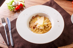 Pasta spaghetti carbonara on white background. Top view. Spaghetti al dente with parmesan on a white plate royalty free stock image