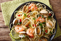 Pasta spaghetti with clam, shrimp, chili and lime close-up. hori royalty free stock image
