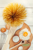 Pasta spaghetti with flour, egg on rustic wooden  background Stock Photo